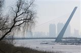 Songhuajiang Highway Bridge over the frozen Songhua River with buildings in the background, Harbin, Heilungkiang Province, China