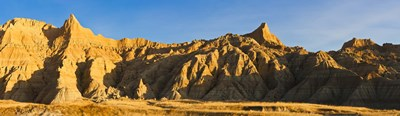Sculpted sandstone spires in golden light, Saddle Pass Trail, Badlands National Park, South Dakota, USA Poster by Panoramic Images for $86.25 CAD