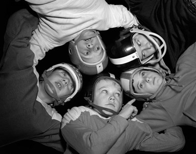 1960s Five Boys In Huddle Wearing Helmets & Football Jerseys Poster by Vintage PI for $66.25 CAD