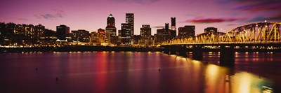 Skyscrapers lit up at sunset, Willamette River, Portland, Oregon, USA Poster by Panoramic Images for $86.25 CAD