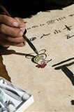 Chinese calligrapher painting calligraphy on a paper at the Dongba Place, Old Town, Lijiang, Yunnan Province, China