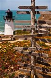 Directional signs on a pole with light house in the background, Point Montara Lighthouse, Montara, California, USA