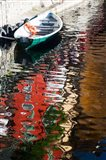 Houses and boat reflected in Lake Como, Varenna, Lombardy, Italy