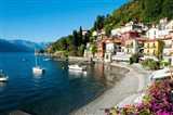 Houses at waterfront with boats on Lake Como, Varenna, Lombardy, Italy