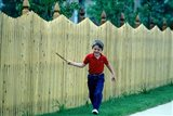 1980s Smiling Boy Running Along Sidewalk