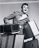 1950s Smiling Bellboy Carrying Four Bags Of Luggage