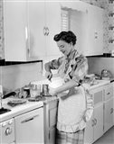 1950s Housewife In Kitchen Mixing Ingredients
