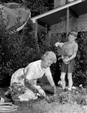 1960s Boy Helping Grandmother Plant Flowers