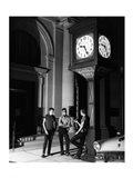 Young men standing below clock at night Art Print